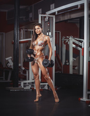 Wall Mural - Sexy athlete girl in bikini with a dumbbells in the gym