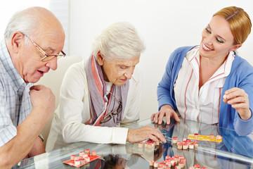 Senior couple playing Bingo with eldercare assistant