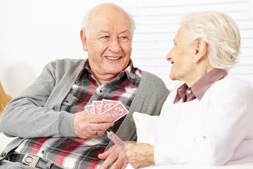 Two senior citizens playing cards