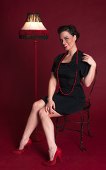 Pinup Girl in Black Dress Smiles Next to Fringed Lamp