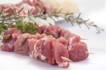 fresh pork skewers with vegetables, onions and rosemary