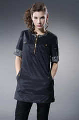 fashion model in black clothes posing in light background