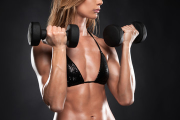 Close up of fit muscular woman lifting dumbbells.