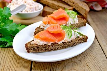 Sandwich with salmon and cream in a dish with cucumber