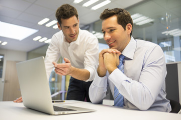 Two handsome businessmen working together on a laptop ,office