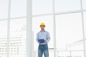 Young architect in yellow hard hat with clipboard in office