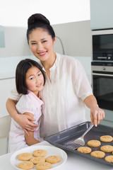 Mother hugging daughter while preparing cookies in kitchen