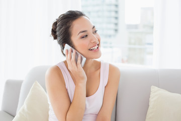 Relaxed happy woman using cellphone on sofa