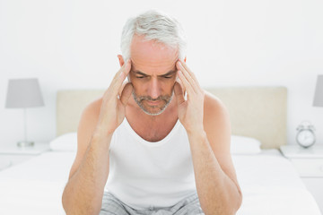 Mature man suffering from headache in bed