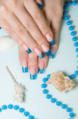 Fingernails with blue french manicure on decorated background