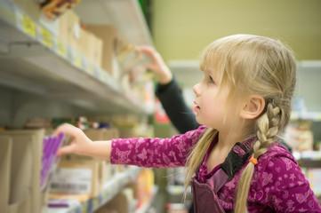 Adorable girl select chocolate bars on shelf in supermarket