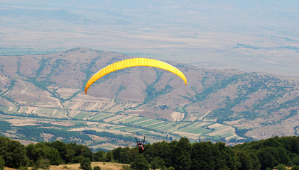Yellow paraglider on the sky