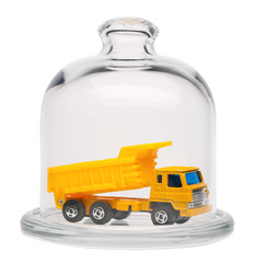 Toy dump truck in a glass dome.