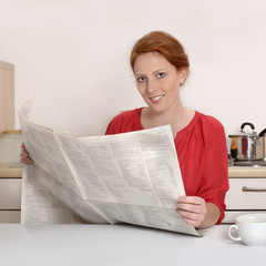 Hübsche rothaarige Frau liest Zeitung