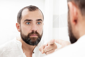 Portrait of a man looking in the mirror