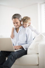 father and son playing on a computer