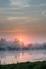 Sun rising above a foggy bog