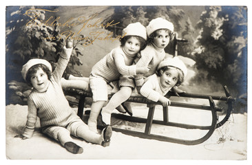 old photo of kids with sledge. vintage christmas postcard