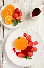 Orange terrine with strawberry sauce and strawberries.