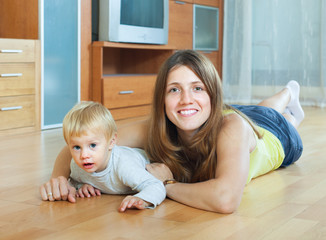 happy mother and child on wooden floor