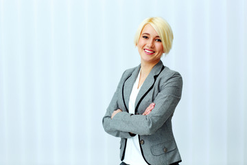 Young beautiful smiling businesswoman with arms folded in office