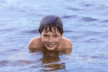 Little boy swimming in a lake