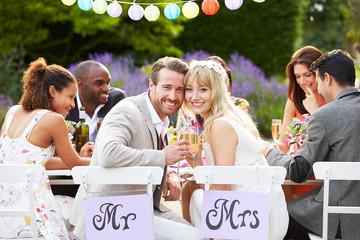 Bride And Groom Enjoying Meal At Wedding Reception