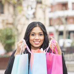 A shoping smiling attractive woman holding shopping bags.