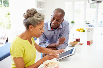 Mature African American Couple Using Digital Tablet At Home