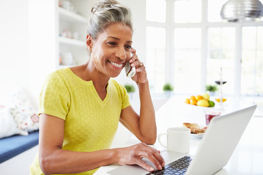 Woman Using Laptop And Talking On Phone In Kitchen At Home