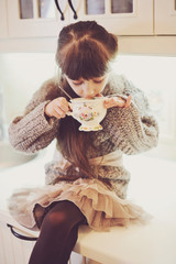 Child girl with a white cup of hot drink