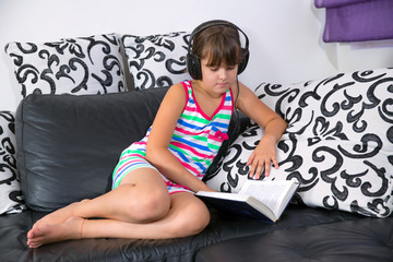 girl listening to music with headphones and reading a book