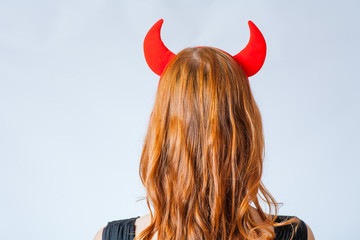 close up of a red haired girl with horns like a devil