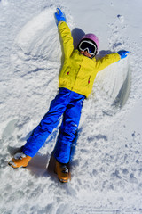 Winter fun - Snow Angel -  skier girl playing in snow