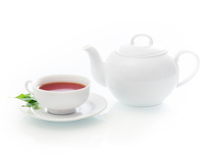 Freshly poured cup of hot tea with a teapot