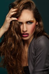 Beautiful portrait. Bright makeup. Girl with hand in hair.