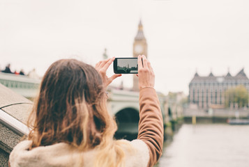 Young woman taking a photo with her phone in London