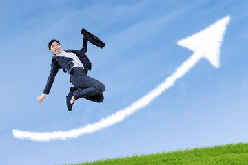 Successful businesswoman jumping with arrow sign
