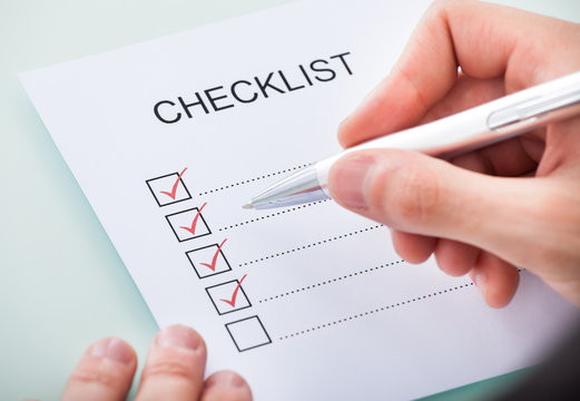 Person's Hand Marking On Checklist With Pen