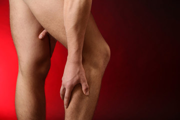 Young man with leg pain, on red background