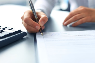 Businesswoman sitting at office desk signing a contract