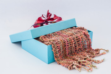 blue gift box with red ribbon and  Striped scarf on isolated whi
