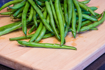 Green beans on a wooden cutting board