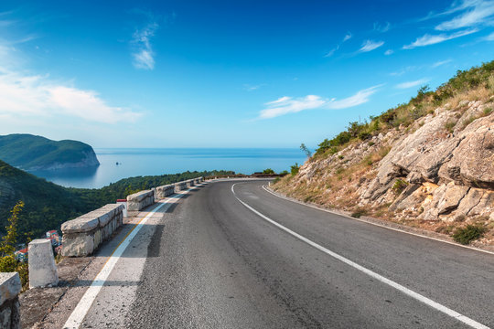 Turning mountain highway with blue sky and sea on a background