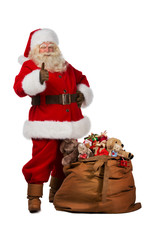 Santa Claus posing near a bag full of gifts and thumbs up