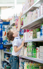 Little boy chooses cosmetics on the shelves of the market