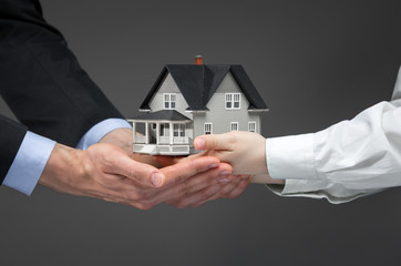 Close up of hands giving house model to other hands