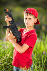 Boy holding a gun in the field.