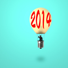 Man taking glowing lamp balloon with 2014 word on it