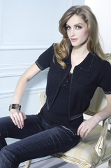 Girl in jeans with black dress sitting in old chair studio shoot